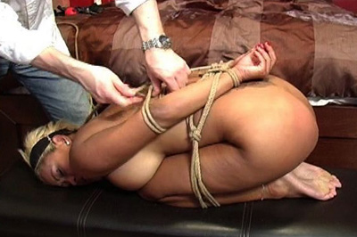 Hogtied babe blows dick. Her master has this blonde bitch hogtied, her hands tied behind her back, her legs folded doubled up