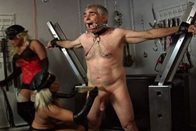 Chained and gagged  with his dick tied up his mistress then proceeds to tie up a considerable piece of chain around his neck a nd lets it hang down and touch his cock. With his penish tied up, his dominatrix then proceeds to tie up a voluminous piece of chain around his neck a nd lets it hang down and touch his cock.